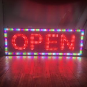 "says""OPEN"" on the sign in red"